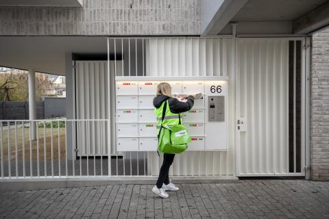 Female courier puts advertising brochures in letterbox