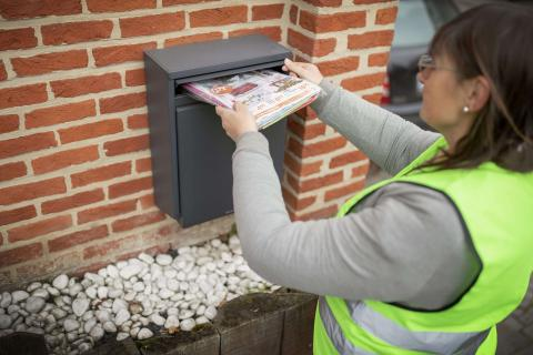 Woman putting brochures in a mailbox.
